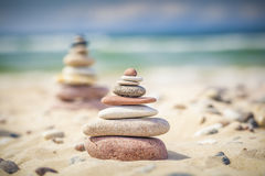 Balanced stones stacked in pile on a sand near sea Stock Photo