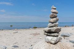Balanced stones stacked to a tower on the beach of the Baltic Se. A against blue sky with copy space royalty free stock photo