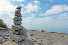 Balanced stones stacked to a tower on the beach of the Baltic Se. A in front of blue sky with white clouds royalty free stock image