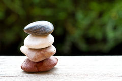 Balanced stones. Standing tall on a wooden table stock image