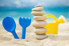 Balanced stones with toy rake, shovel and watering-cans near sea Stock Photography