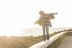 Hippy woman in balance walking near the ocean. Balanced walk for hippy woman with a poncho and jeans. ocean view in the coastline with horizon and clear sky sith Royalty Free Stock Image