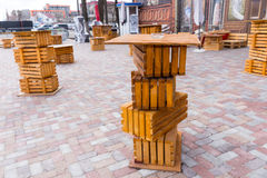 Balanced wooden crates forming tables. Outdoors on a brick paved courtyard in front of a commercial building royalty free stock photography