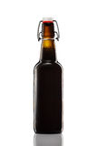 Balancee la botella superior de cerveza oscura aislada en el fondo blanco imagen de archivo