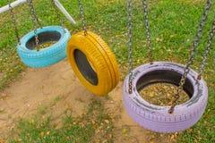 Balancee las sillas hechas de los neumáticos viejos para los niños en parque fotos de archivo libres de regalías