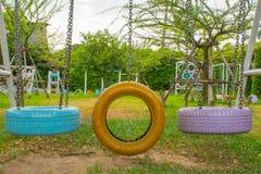 Balancee las sillas hechas de los neumáticos viejos para los niños en parque foto de archivo libre de regalías