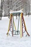 Balancee para los niños en el parque en invierno Imagen de archivo libre de regalías