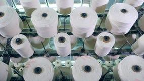 Balanceo blanco de la fibra en las bobinas, colocadas en un estante de la fábrica metrajes