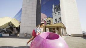 Balanceo de la muchacha en silla coloreada cerca del edificio de oficinas almacen de video