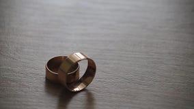 Balanceo del anillo de bodas del oro del hombre a la mujer una en una tabla metrajes