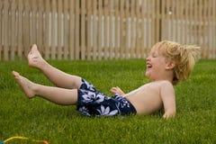 Balanceo joven del muchacho en la hierba Imágenes de archivo libres de regalías