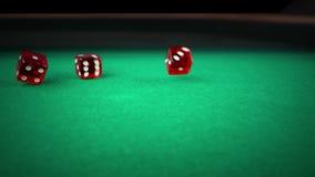 Balanceo rojo de tres dados en la tabla de juego del juego verde en el fondo negro, tirando con la cámara lenta, concepto de reco almacen de metraje de vídeo