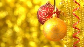 Balanceo rojo y de oro de las bolas de la Navidad Decoración del Año Nuevo Bokeh de oro borroso almacen de video