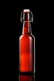 Balancez la bouteille supérieure de bière blonde d'isolement sur le fond noir Photos stock