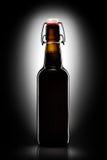 Balancez la bouteille supérieure de bière blonde d'isolement sur le fond noir Photographie stock libre de droits