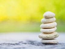 Balancieren Sie die Steine, die zur Pyramide im weichen grünen Hintergrund gestapelt werden Stockbild