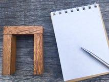 Balancieren Sie Holzklotz neben Notizbuch und Stift für Projekt im Geschäftsteam Lizenzfreie Stockbilder
