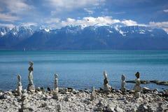 Balancieren Sie Steine auf dem See mit Ansichten der Berge Stockfotos