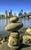 Balancierende Felsen gegen Stadt-Skyline Lizenzfreies Stockbild