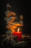 Balancierende Steine mit einer Kerze Stockfotografie