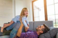Balancierende Tochter des spielerischen Vaters auf Beinen oben auf Sofa stockfotografie