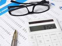 Balancing the accounts. Calculator,glasses and pen on financial documents Royalty Free Stock Images
