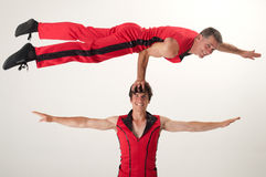 Balancing acrobat. An acrobrat balances with one arm on the head of his acrobat partner royalty free stock photos