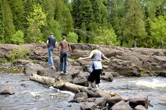 Balancing Act. Young people crossing a stream on a log Stock Photo