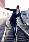 Balancing Act. Attractive woman balancing as she walks on railroad rails Royalty Free Stock Photos