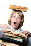 Balancing Act. A surprised boy holds a book open while balancing another book on his head Stock Photo