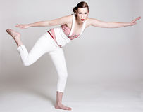 Balancing act. Beautiful woman standing on one leg and in balance Stock Images