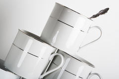 Balancing Act. Stack of white porcelain cups with the spoon in the top one Royalty Free Stock Image
