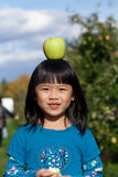 Balancing an Apple. Young girl balancing an apple on her head at an apple orchard with golden delicious apples on the trees Royalty Free Stock Photography