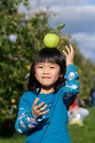 Balancing an Apple. Young girl balancing an apple on her head at an apple orchard with golden delicious apples on the trees Royalty Free Stock Image