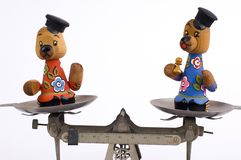 Balancing Bears. A laboratory balance scale on white background with a pair of wooden bears in balance Royalty Free Stock Photography