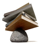 Balancing The Books On A Rock. A pile of leather books balancing on a rounded stone on an  background Royalty Free Stock Photography