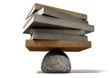 Balancing The Books On A Rock. A pile of leather books balancing on a rounded stone on an  background Royalty Free Stock Images