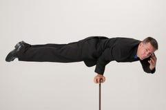 Balancing businessman talking on cell phone Royalty Free Stock Image