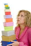Balancing gifts. Young woman holding a stack of gift boxes stock image