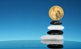 Balancing gold one dollar on stack of stones. Zen Royalty Free Stock Image