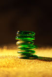 Balancing green glass stones. Green glass stones on golden sand,shallow DOF Royalty Free Stock Photography