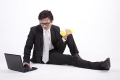 Balancing life between work and workout. Asian businessman works on his laptop while lifting dumbbell Royalty Free Stock Images