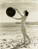 Balancing a medicine ball on the beach Stock Photography