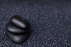 Balancing peaceful black stones in the relaxing Zen garden Royalty Free Stock Photography
