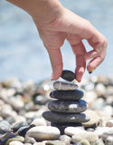 Balancing pebble tower. With female hand Stock Photos