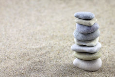 Balancing pebbles. Placed on sand Royalty Free Stock Image