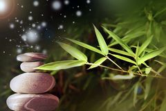 Effect of Zen meditation. Balancing pebbles and bamboo. Zen atmosphere with lights effect royalty free stock photos