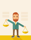 Balancing priorities. A hipster Caucasian businessman with beard carrying a balance scale with both hands weighing want and need. Balancing and priorization Royalty Free Stock Image