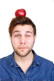 Balancing red apple on head. Portrait of a young man balancing red apple on head Stock Image