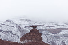 Balancing Rock in Front of Snowy Mountain. A rock balancing on a small formation in front of a ridged snowy mountain in Utah Royalty Free Stock Images